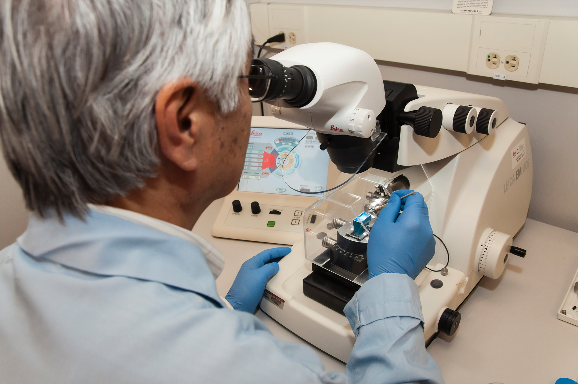 A technician using a microtome at the Advanced Technology Research Facility (ATRF), Frederick National Laboratory for Cancer Research, National Cancer Institute. A microtome is an instrument that cuts extremely thin sections of material for examination under a microscope.