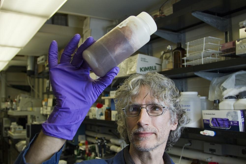 man in purple long sleeve shirt holding white plastic bottle