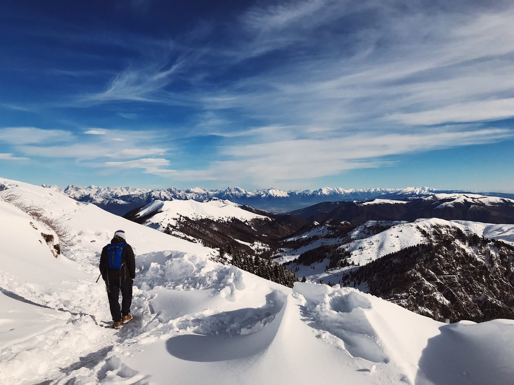 man in blue jacket and black pants standing on snow covered ground during daytime
