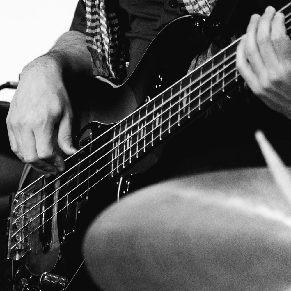 grayscale photo of man playing guitar