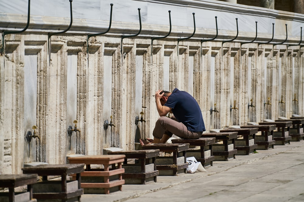 man in blue t-shirt sitting on brown wooden bench during daytime