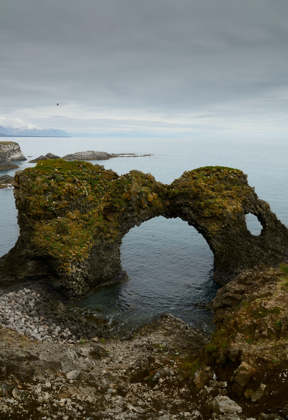 green moss covered rock formation on sea under white clouds during daytime