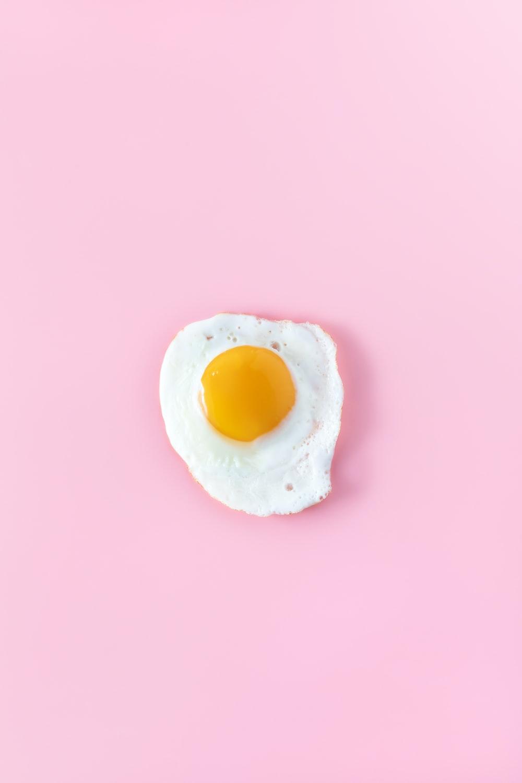 sunny side up egg on pink surface