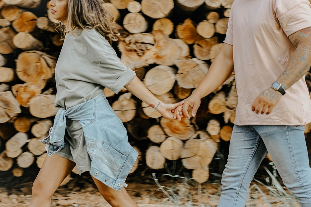 man and woman holding hands while walking on dried leaves