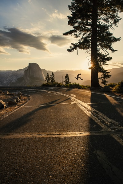 Silhouette of a man jumping in Yosemite National Park during a beautiful sunrise on Glacier Point with Half Dome in the background.