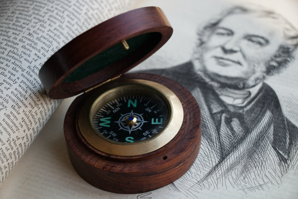 brown wooden framed compass on white textile
