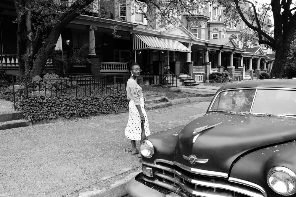 grayscale photo of woman in long sleeve dress standing beside car