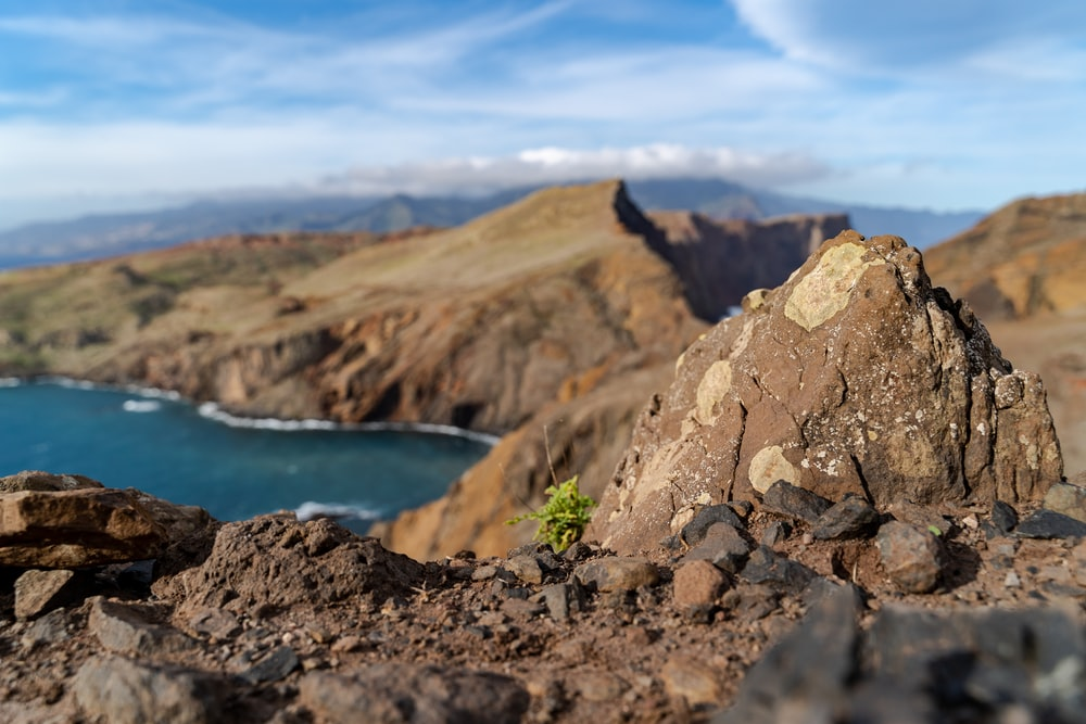 brown rocky mountain beside blue sea under blue sky during daytime