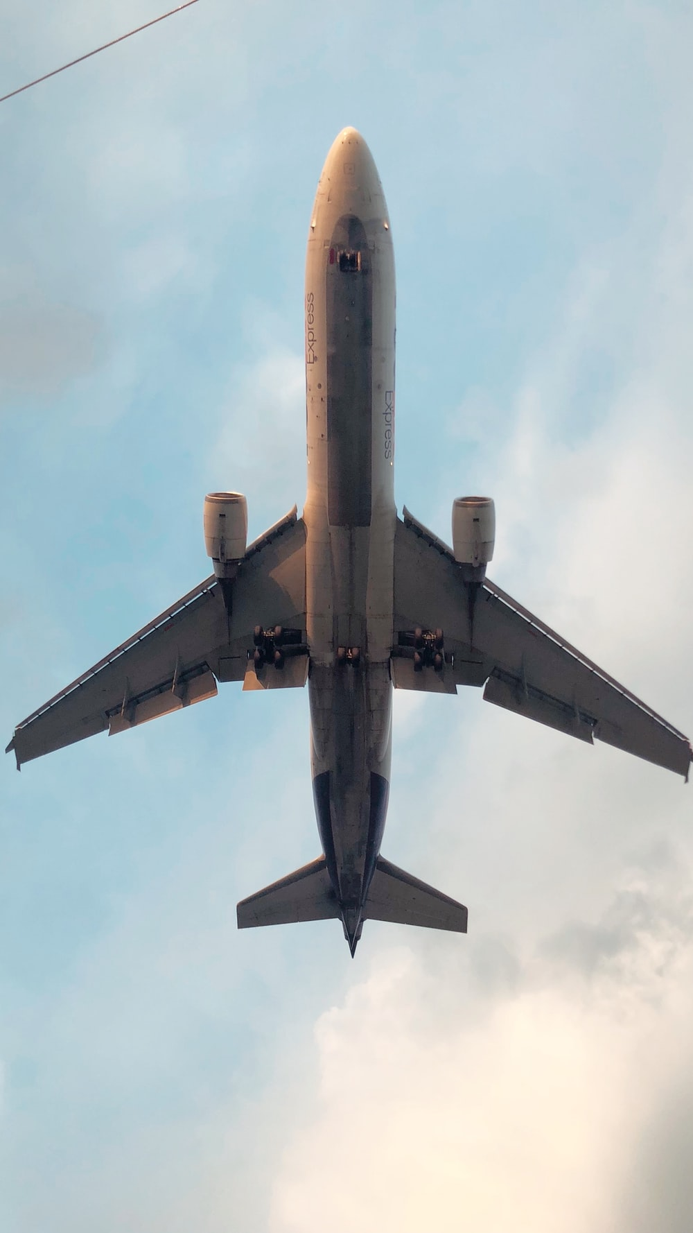 gray and yellow airplane under white clouds during daytime