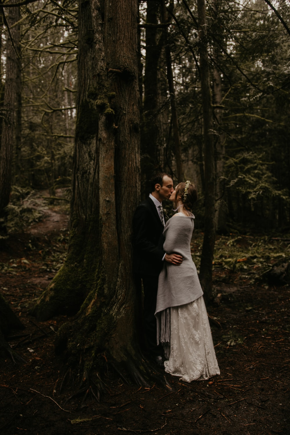 man and woman kissing in forest during daytime