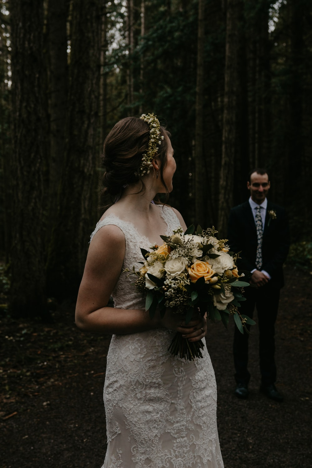 woman in white floral wedding dress holding bouquet of flowers