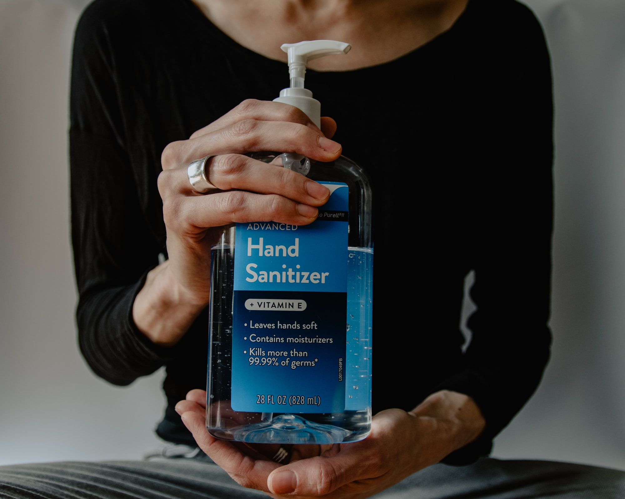 Hands holding a large bottle of hand sanitizer