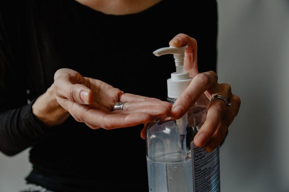 person holding white plastic spray bottle