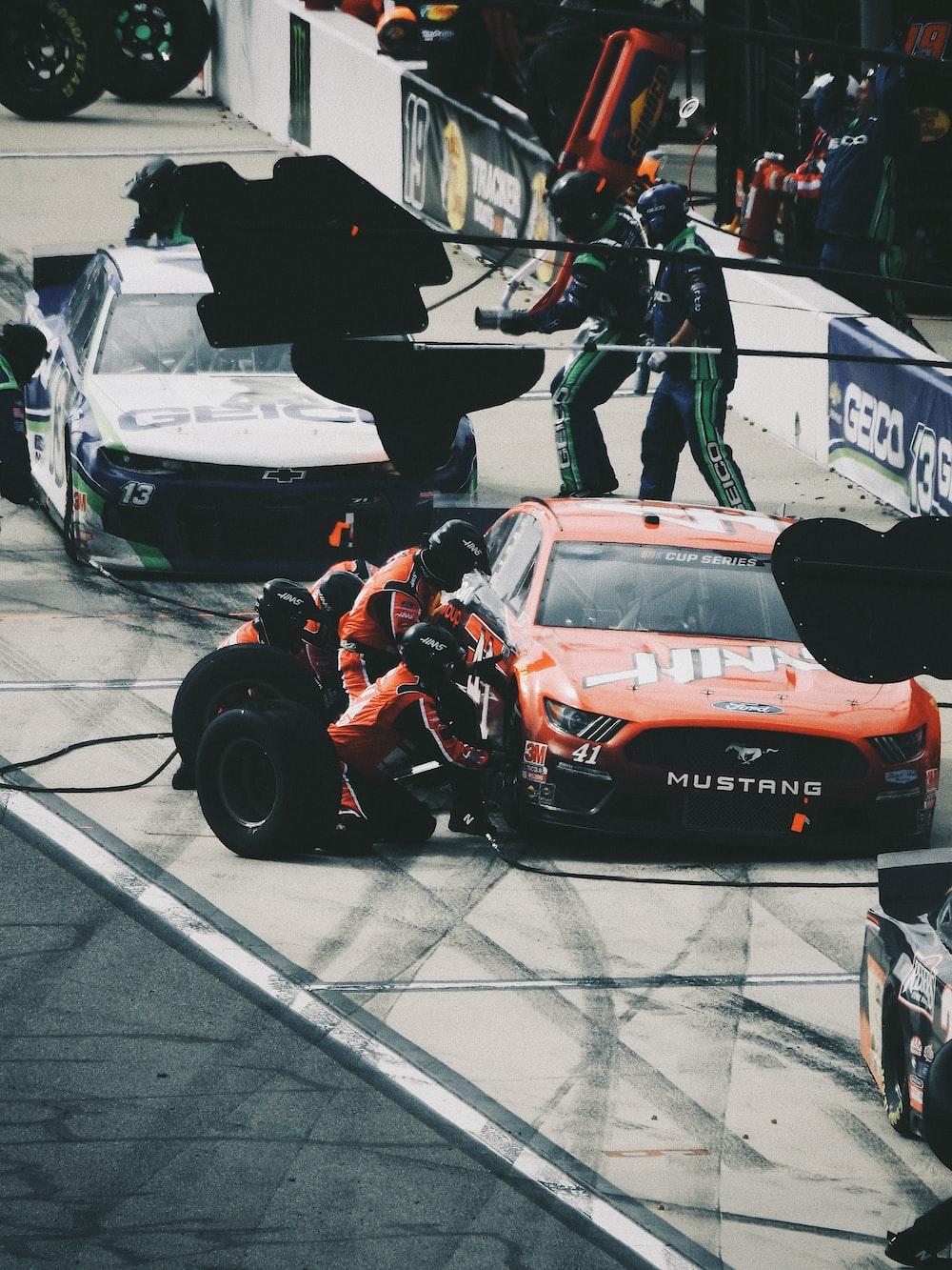 man in black jacket and pants riding orange and black racing car