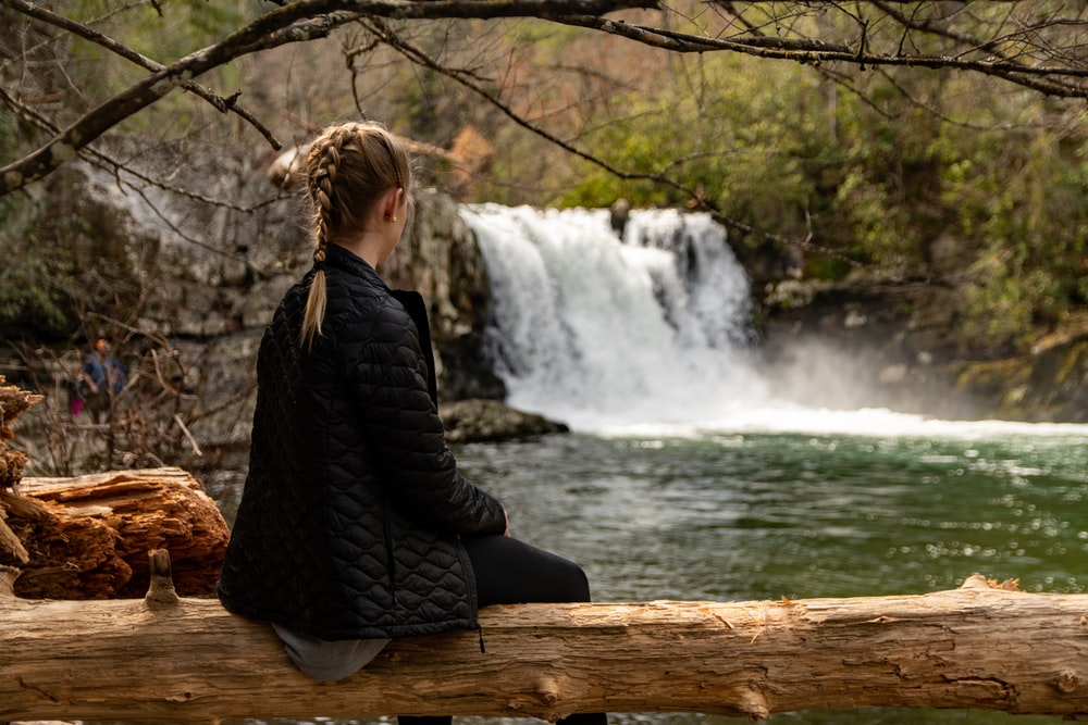 woman in black jacket sitting on brown wooden log near waterfalls during daytime