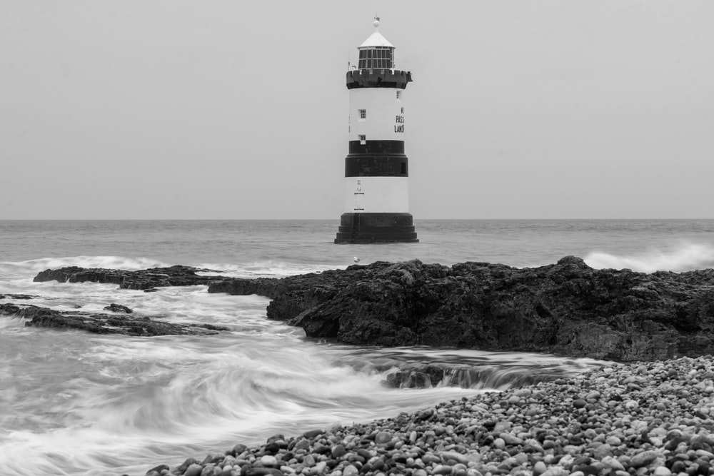 grayscale photo of lighthouse on rock formation near sea