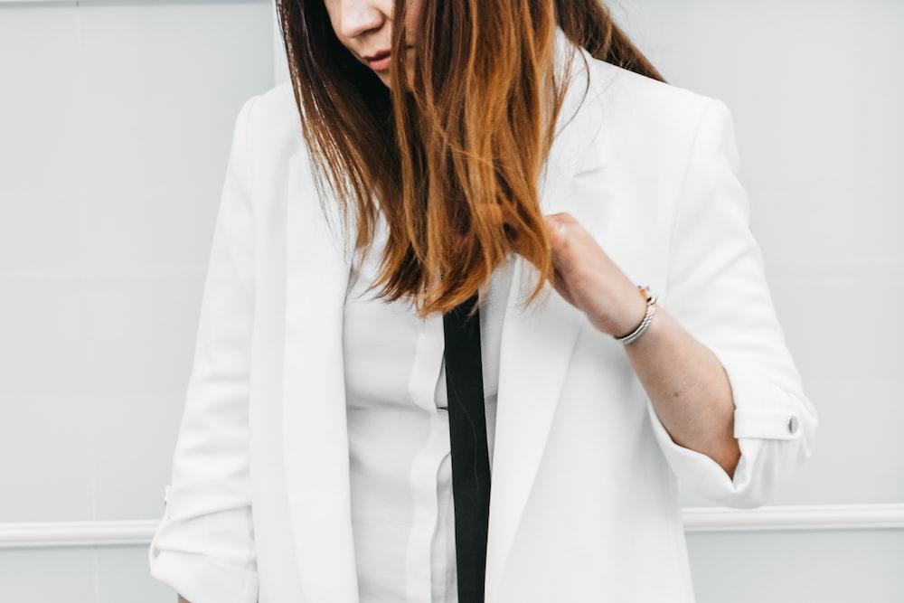 woman in white blazer with black necktie