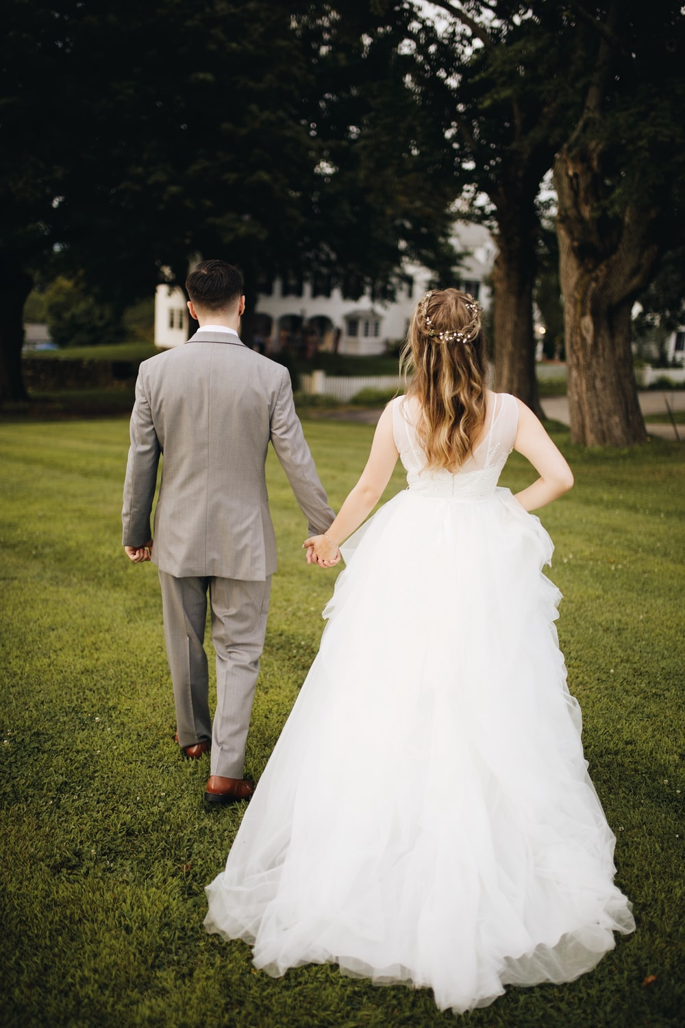 man in gray suit and woman in white wedding dress walking on green grass field during