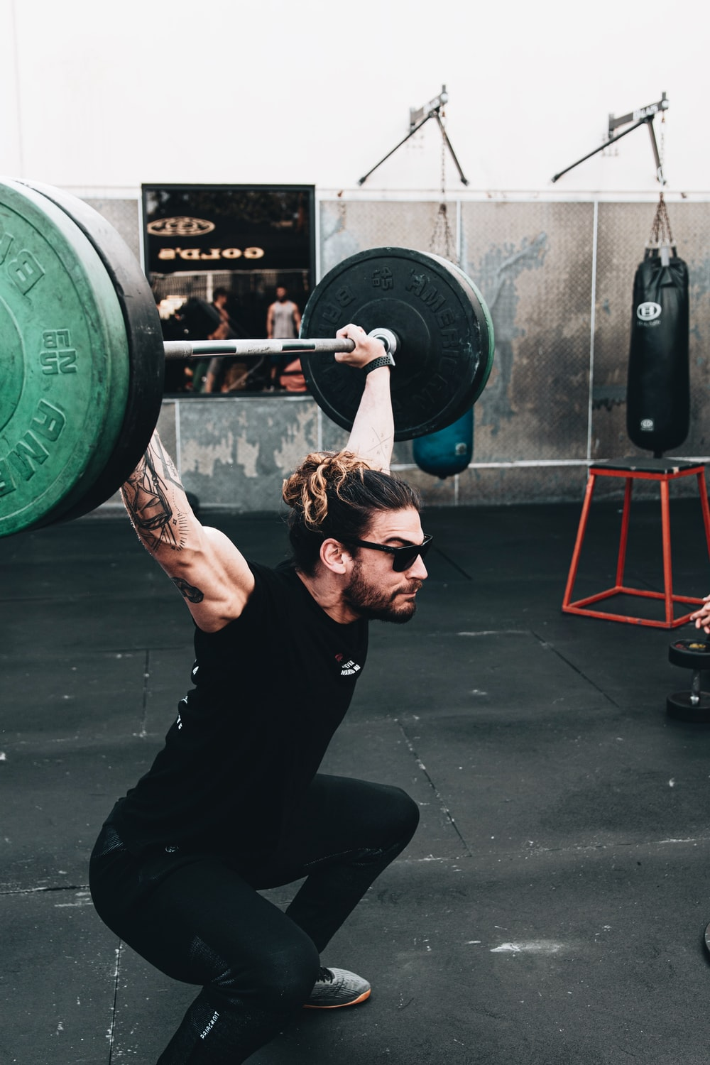 woman in black tank top holding green barbell