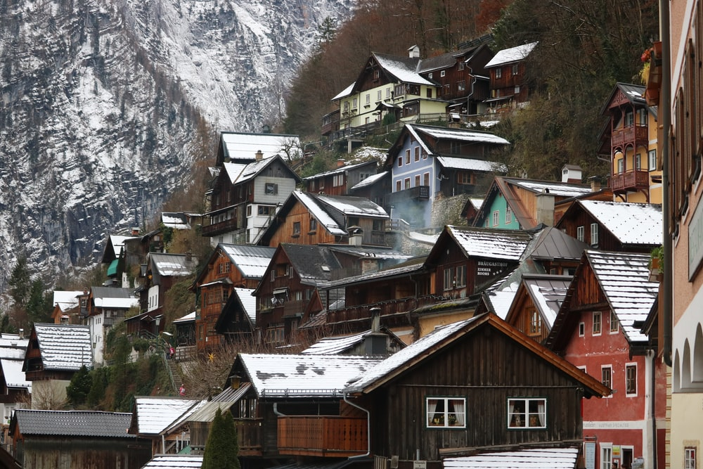 brown and white houses near mountain during daytime