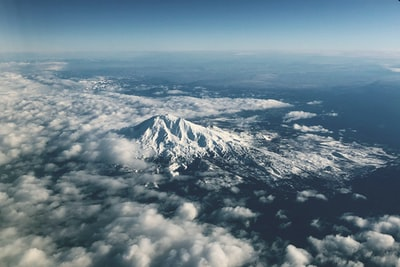 white clouds over snow covered mountain aerial view teams background