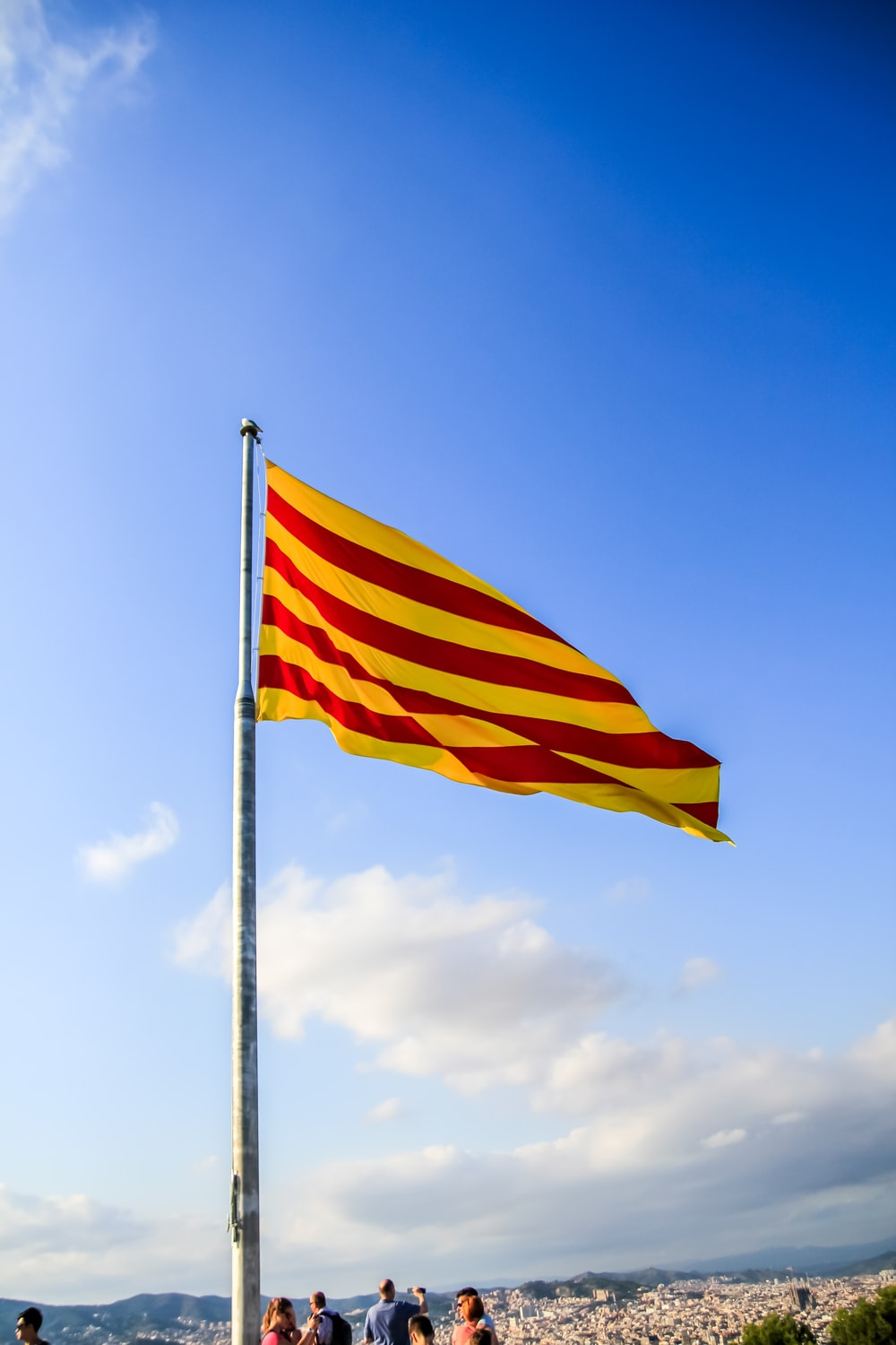 red yellow and white striped flag under blue sky during daytime