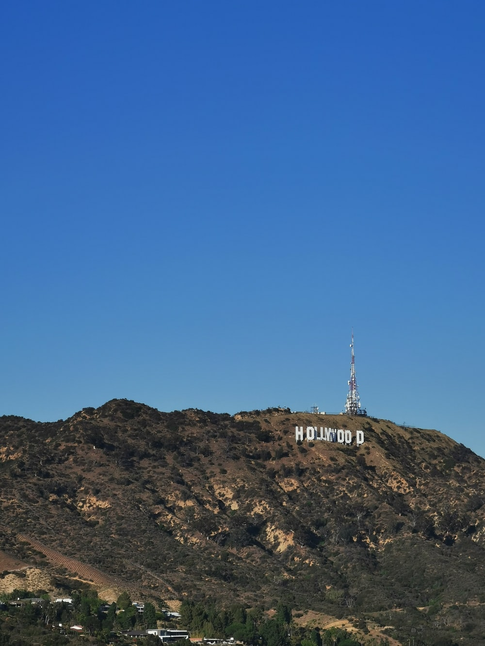 white tower on brown rock mountain under blue sky during daytime