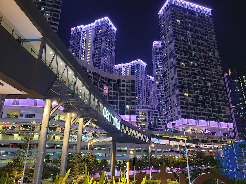 people walking on sidewalk near high rise buildings during nighttime