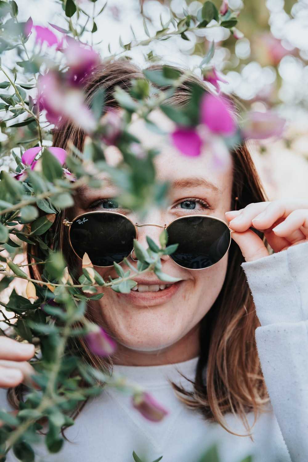 woman in black sunglasses holding green leaves