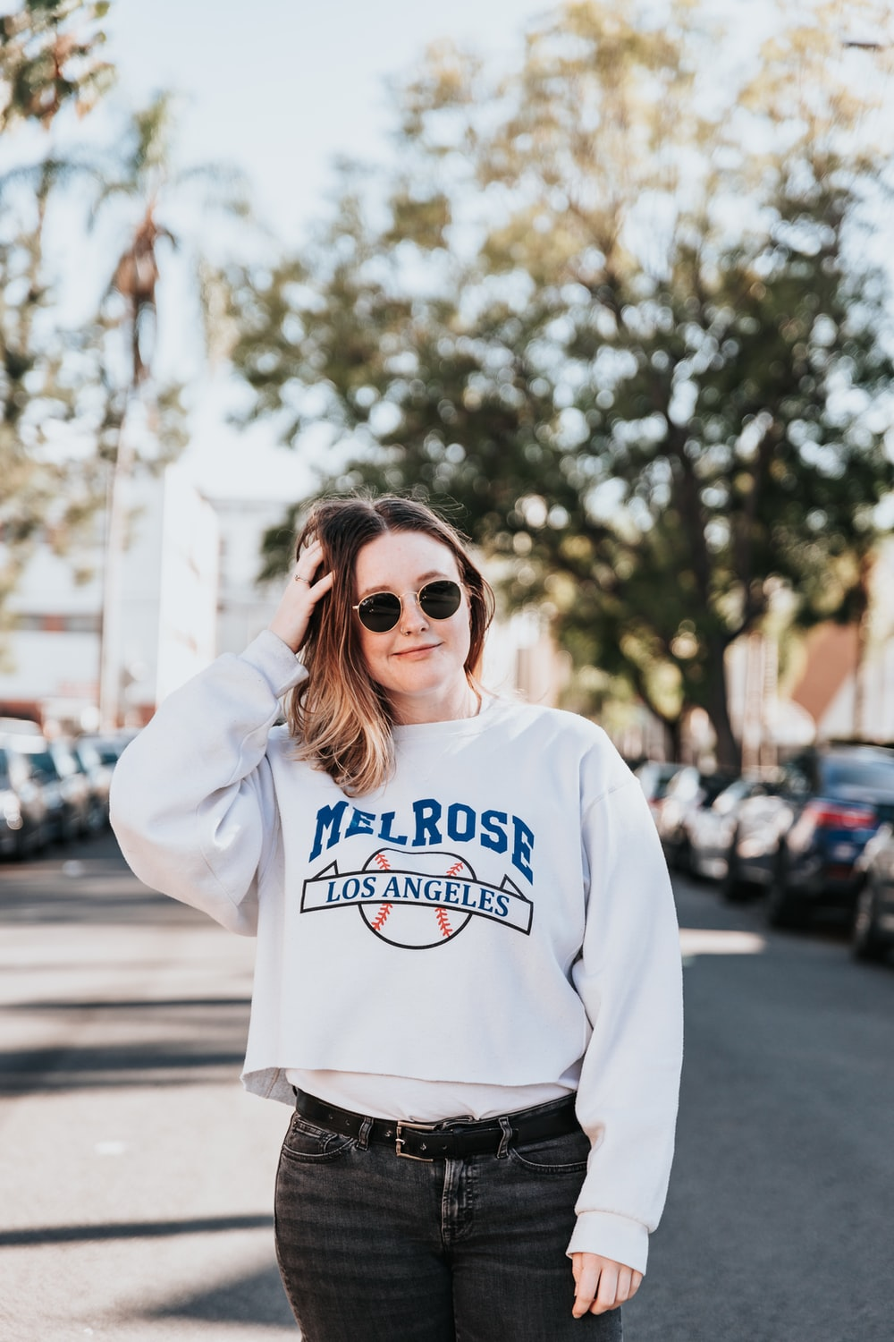 woman in white and blue pullover hoodie wearing brown sunglasses