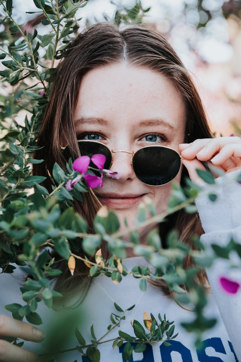 woman in black sunglasses holding green plant