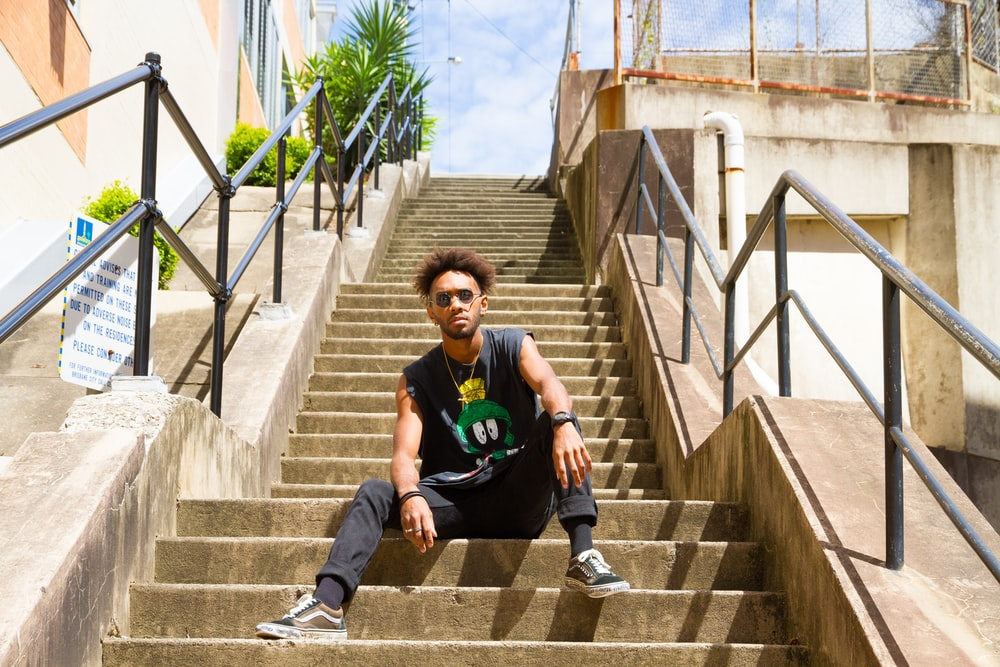 man in black and green crew neck t-shirt sitting on brown concrete stairs during daytime