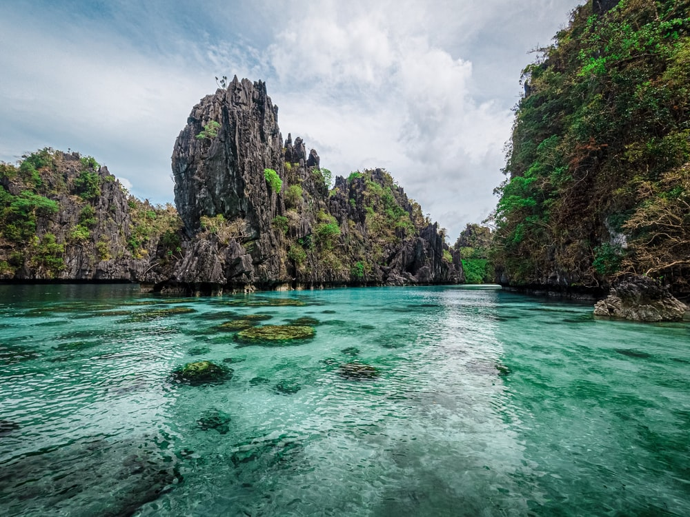 green and brown rock formation on blue sea under white clouds and blue sky during daytime