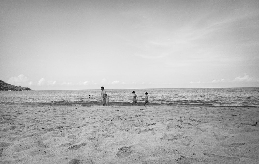 grayscale photo of 2 person walking on beach