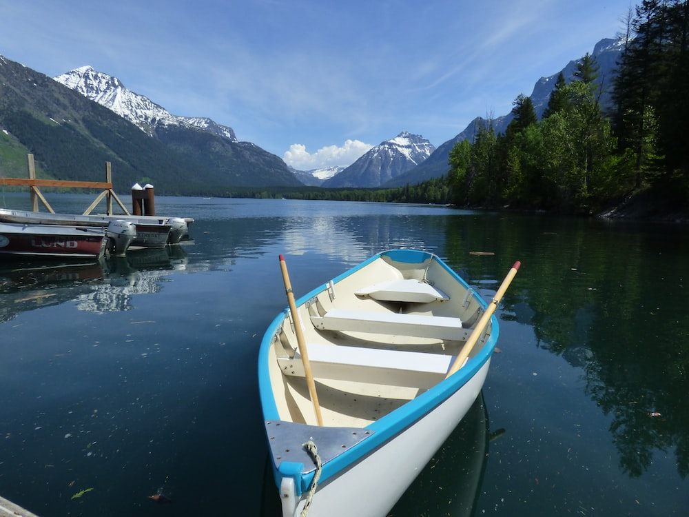 white and blue boat on water near green trees and mountain during daytime