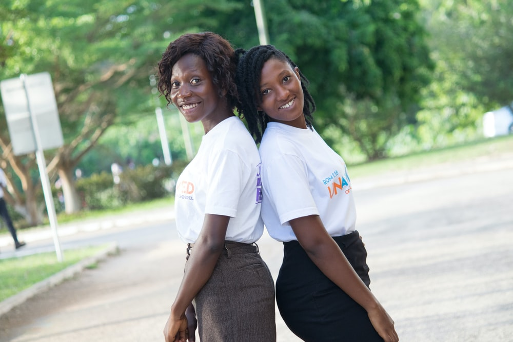 2 women in white polo shirt standing on road during daytime