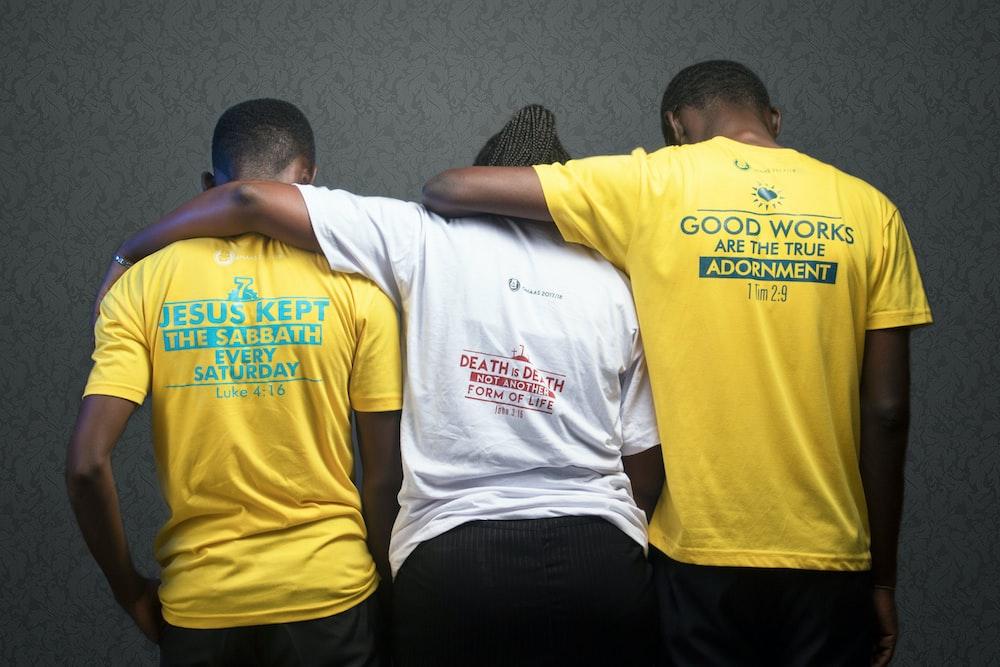 man in yellow crew neck t-shirt sitting beside man in black t-shirt