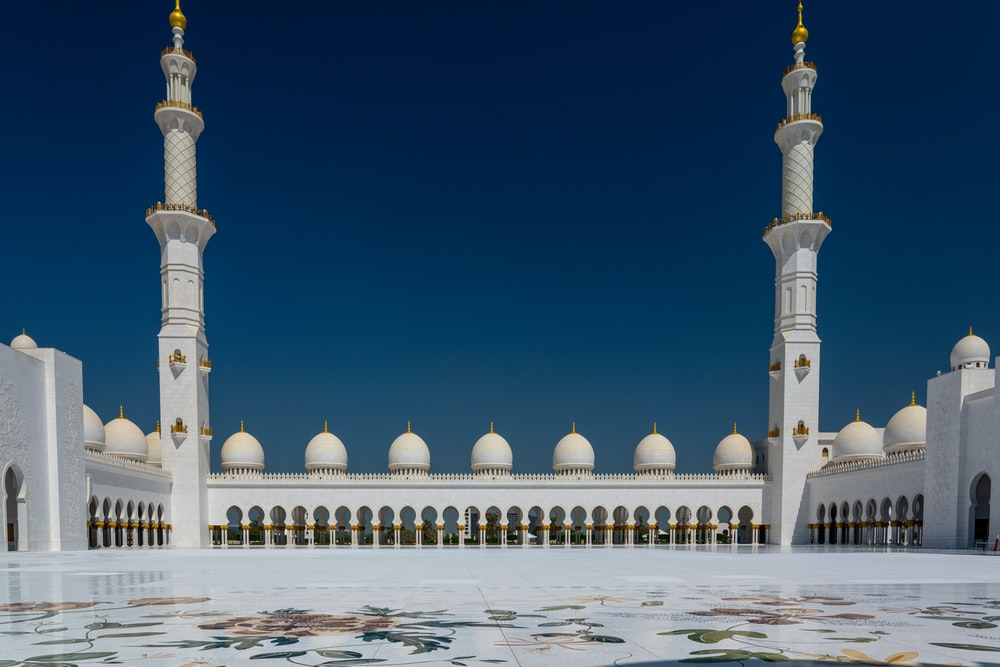 white and gold mosque under blue sky during daytime