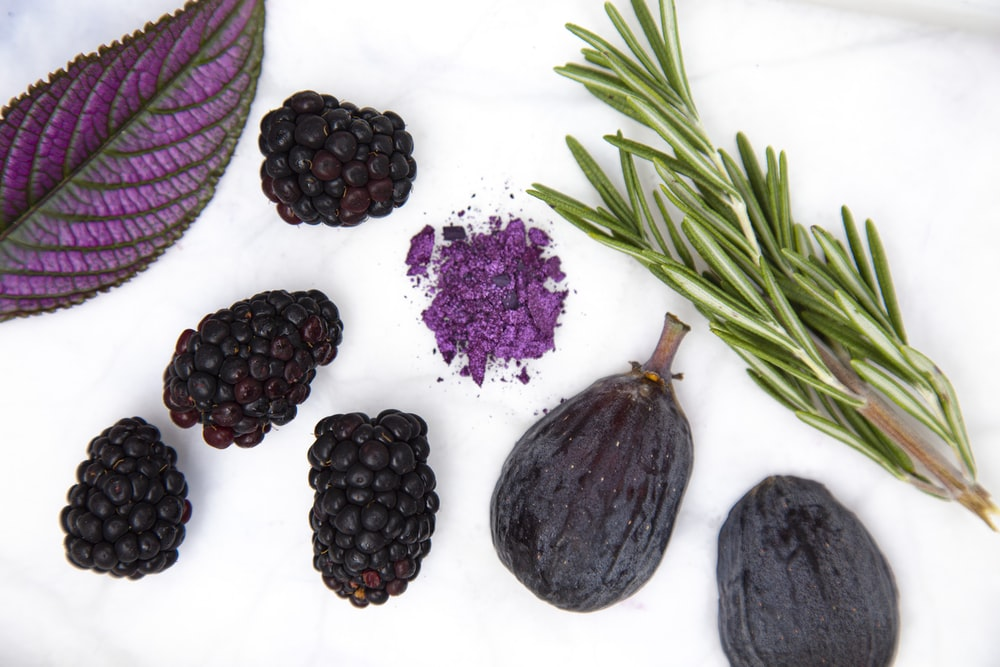 purple round fruit on white surface