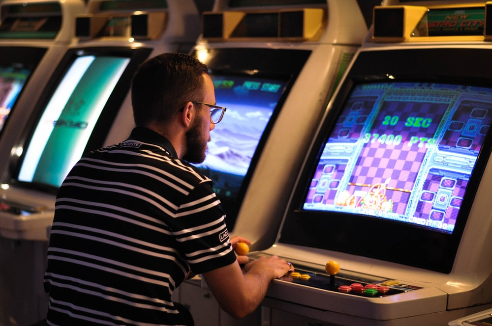 man in black and white striped shirt playing arcade game