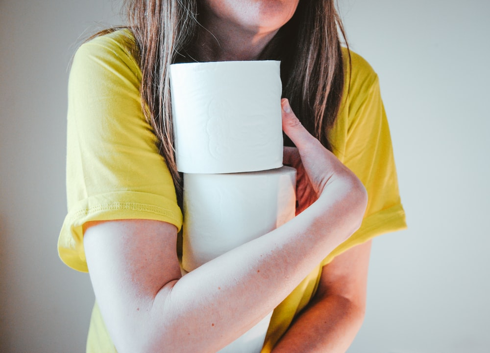 woman in yellow t-shirt holding white tissue paper