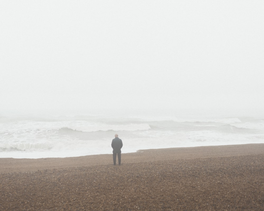 person in gray shirt standing on brown sand near sea during daytime