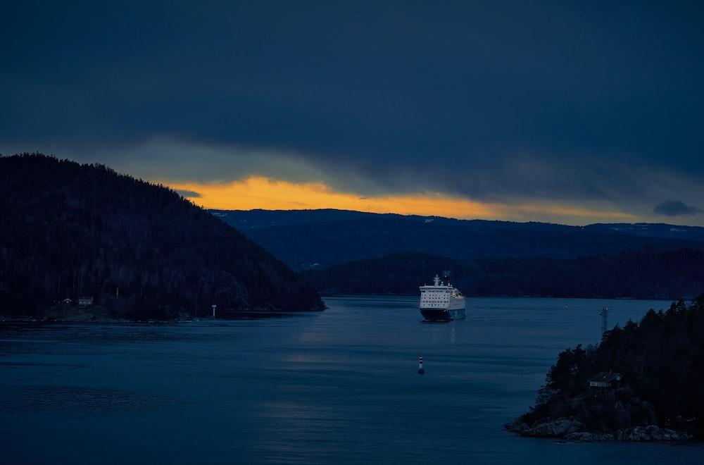 white ship on sea near mountain during daytime