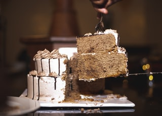 person holding brown and white cake