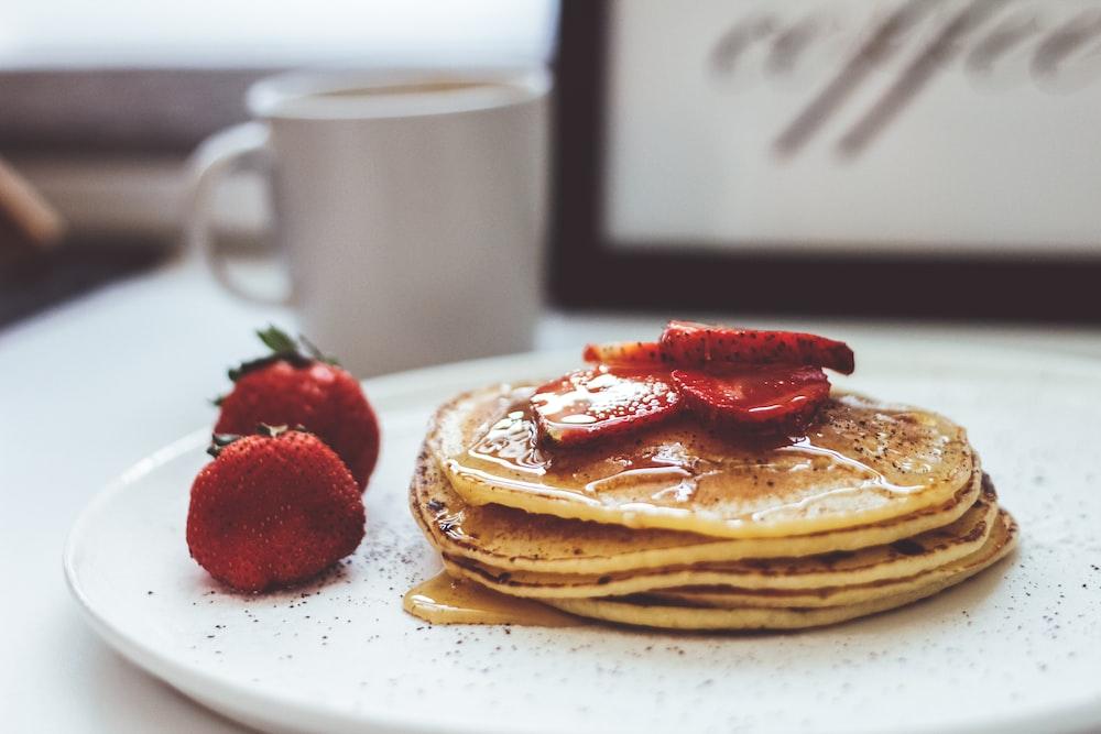 Pancake with strawberry on white ceramic plate