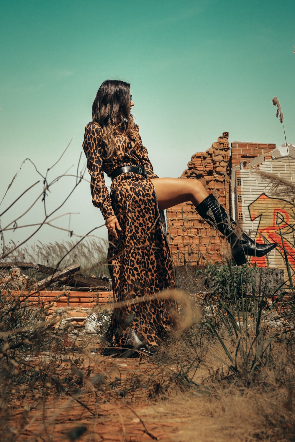 woman in black and brown leopard print dress standing on brown dried leaves during daytime