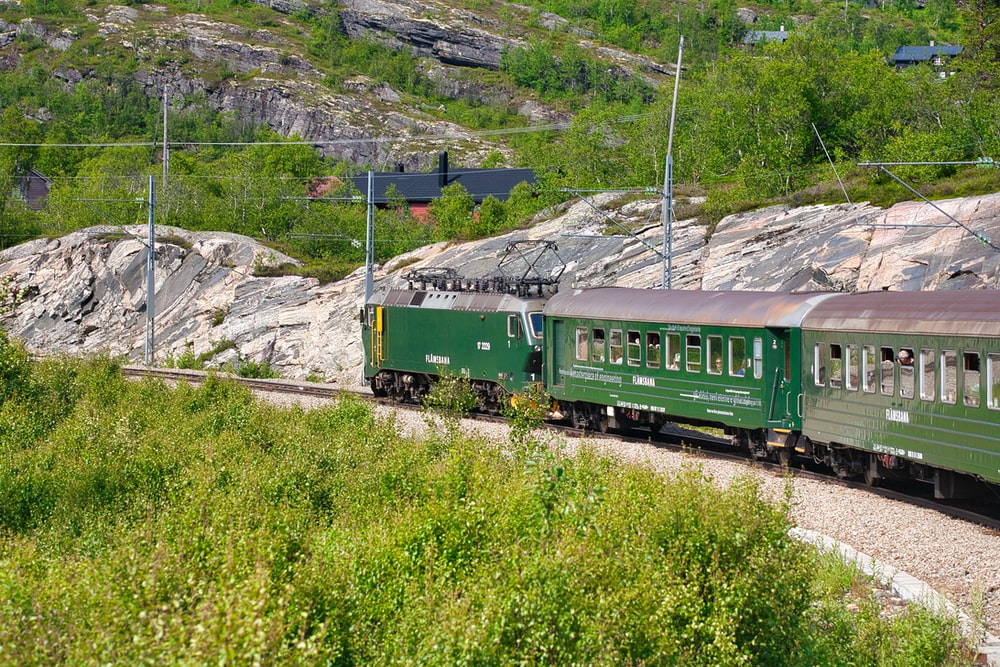 green train on rail tracks during daytime