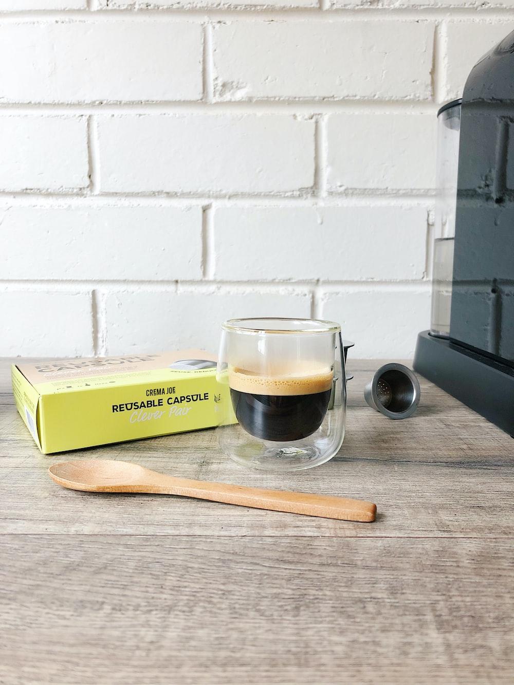 clear glass mug on brown wooden chopping board