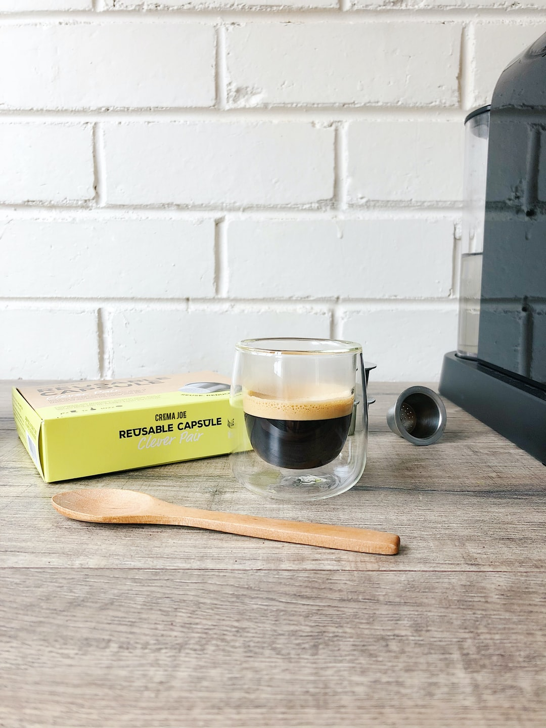 Espresso coffee in clear glass, made with reusable pod and capsule machine