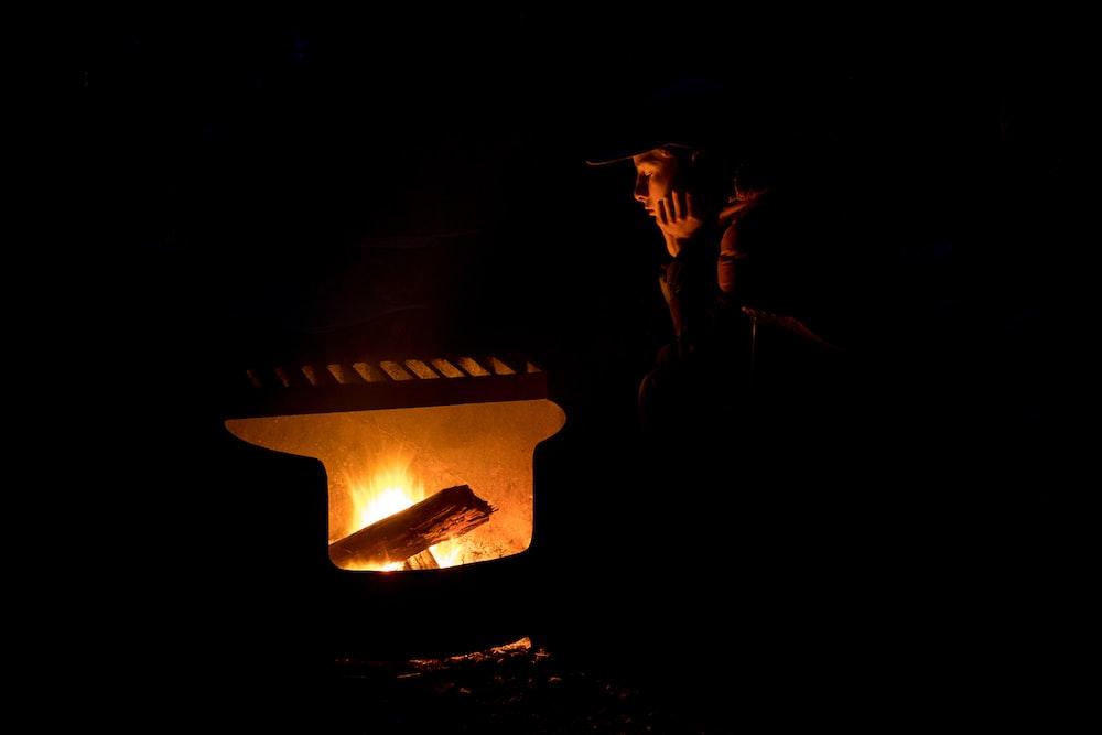 silhouette of man wearing hat standing near fire pit